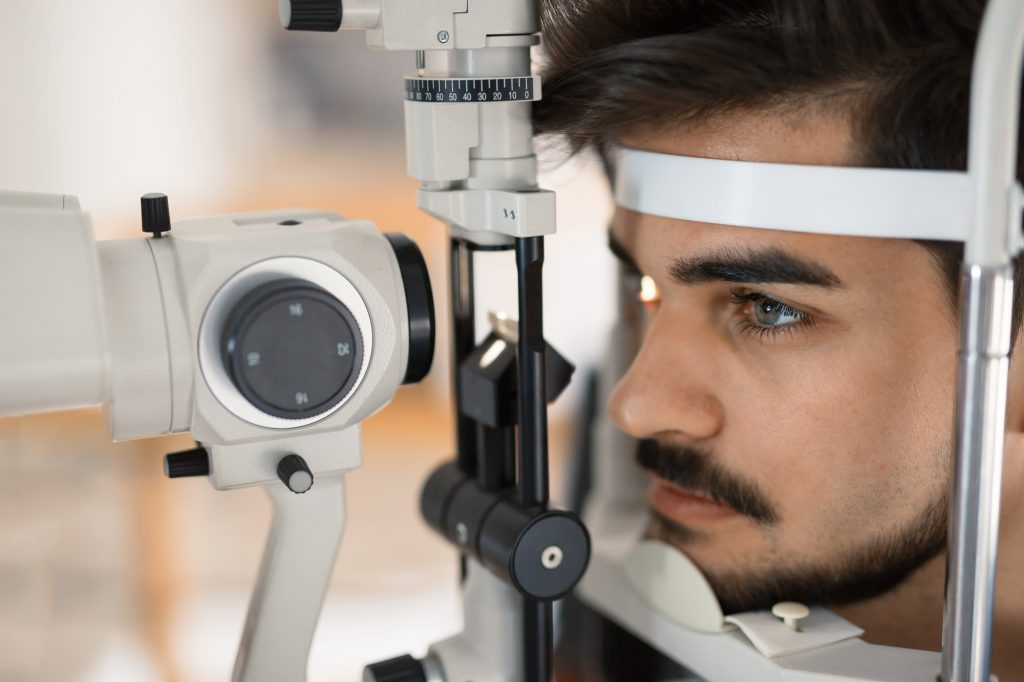 Patient or customer at slit lamp at optometrist or optician