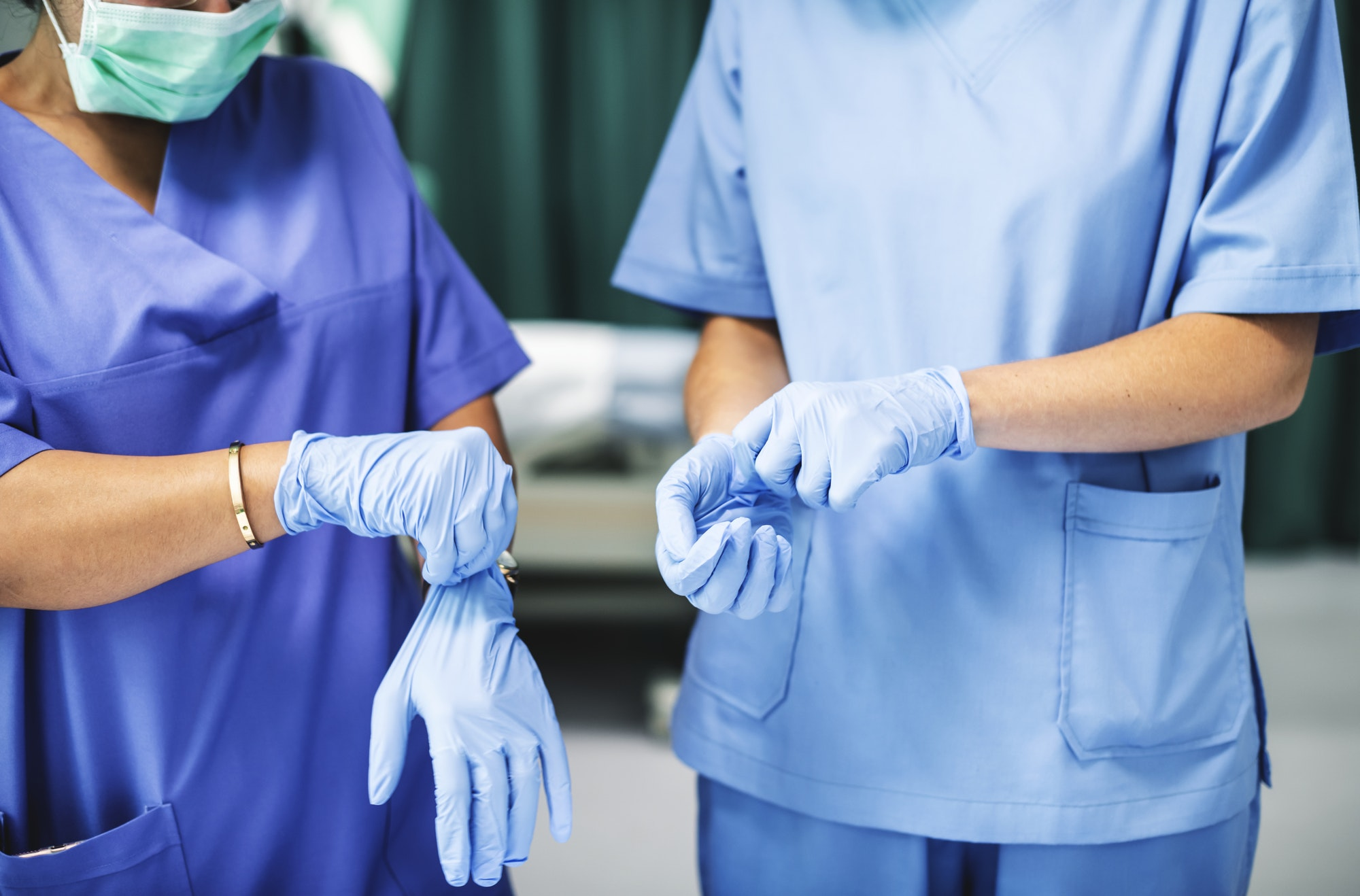 Surgeons wearing gloves preparing for surgery